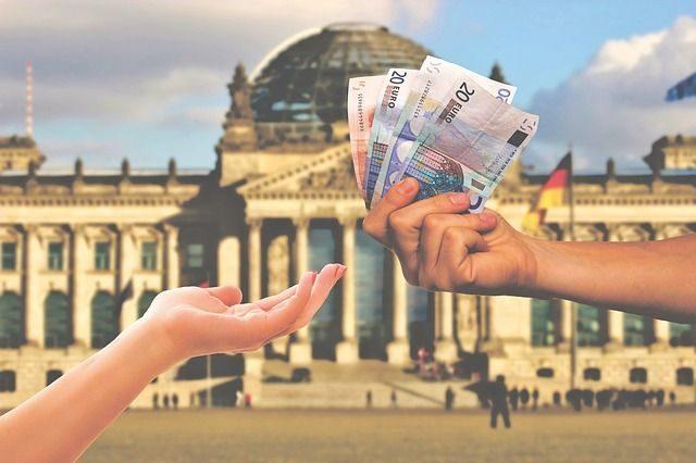 podavanie penazi z ruky do ruky v pozadi budova nemeckeho parlamentu