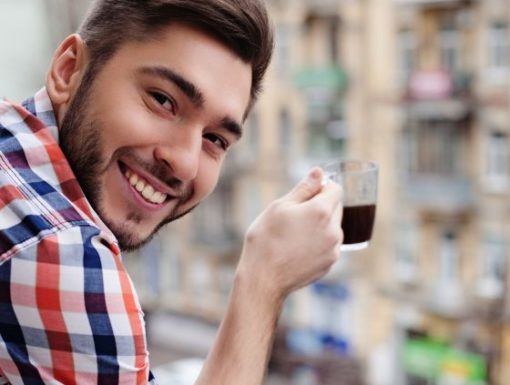 My morning in a big city. Cheerful young man is enjoying hot coffee and smiling. He is standing on balcony and looking at camera happily